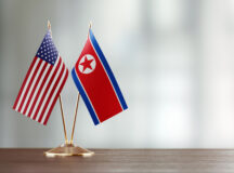 American and North Korean flag pair on desk over defocused background. Horizontal composition with copy space and selective focus.